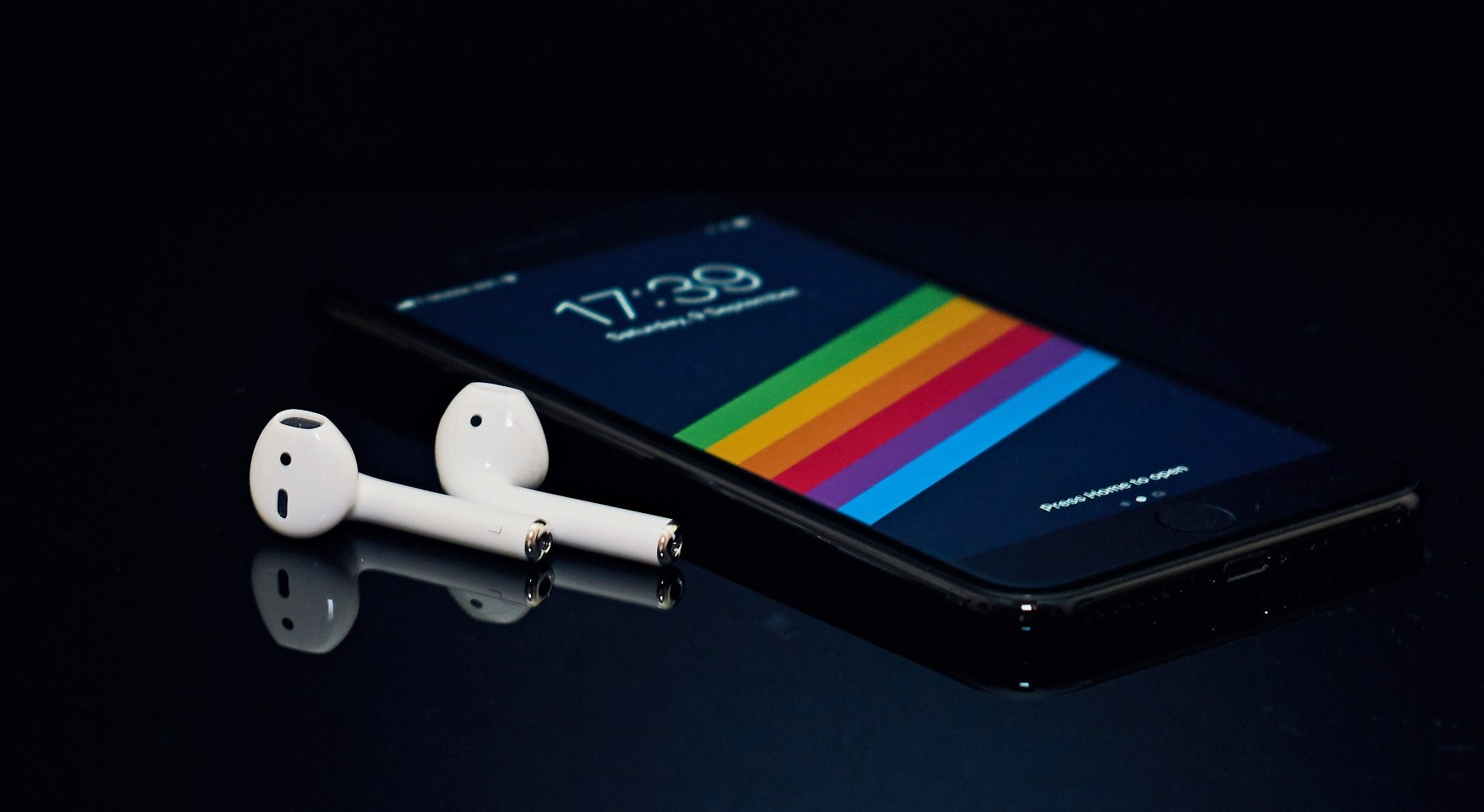 Auriculares Bluetooth Apple AirPods 1 junto a un iPhone